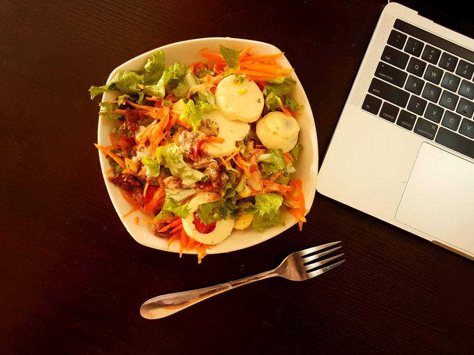 une assiète de salade près d'un ordinateur. Nous n'utilisons plus nos chèques repas pendant le télétravail